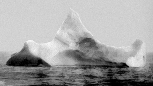 The iceberg thought to have been hit by Titanic, photographed the morning of 15 April 1912 by SS Prinz Adalbert's chief steward. The iceberg was reported to have a streak of red paint from a ship's hull along its waterline on one side.